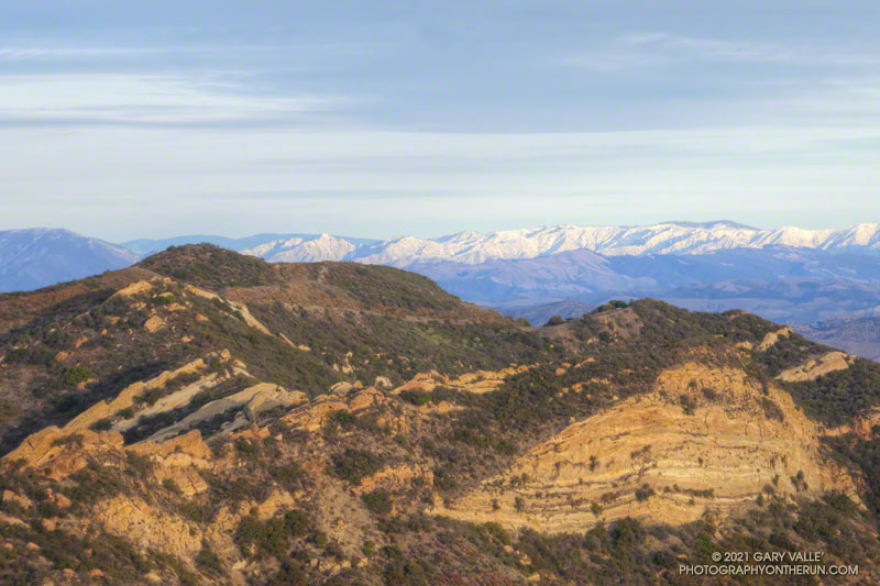 Calabasas Peak (left) with the snowy peaks of Los Padres National Forest in the background. The snow-covered peaks are south of Mt. Pinos and Frazier Mountain, in the area of San Raphael Peak, McDonald Peak, Sewart Mountain and Snowy Peak. January 31, 2021.