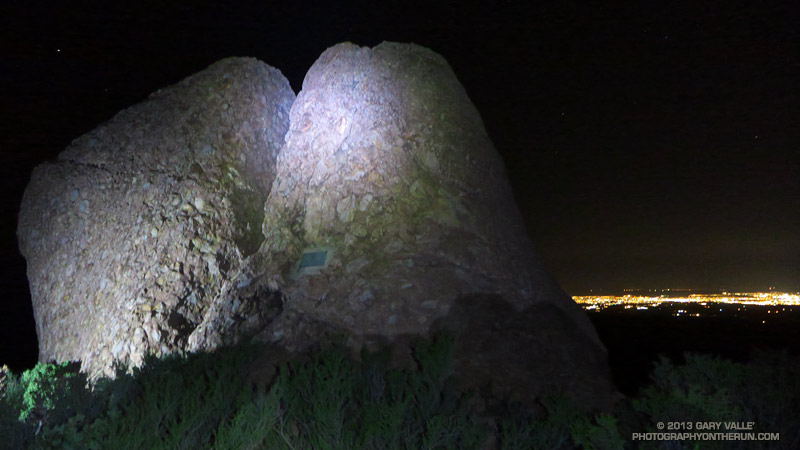 Chamberlain rock and monument on the Chamberlain Trail segment of the Backbone Trail. The lights of Oxnard, Port Hueneme and Ventura are in the distance.