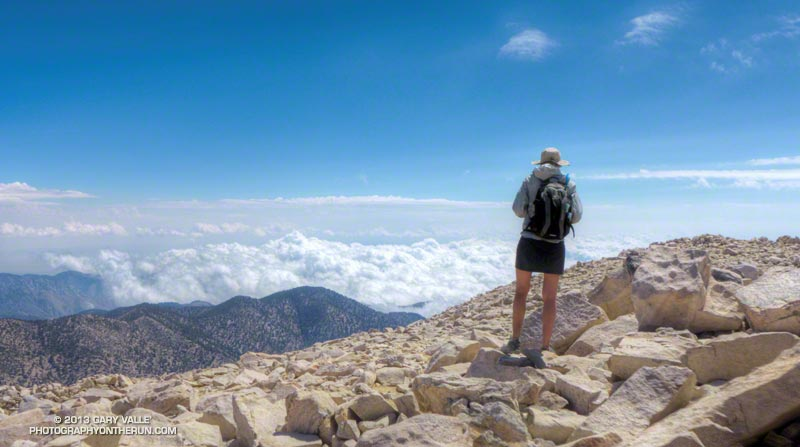 Hiker on the summit of San Gorgonio Mountain. The cumulus clouds are the result of the remnants of Tropical Storm Ivo being entrained in a monsoon flow. The view is east over Whitewater Canyon toward Morongo Valley. August 24, 2013.