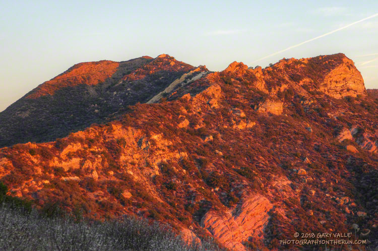 The first rays of sunlight illuminate the rocks and ridges of Calabasas Peak.
