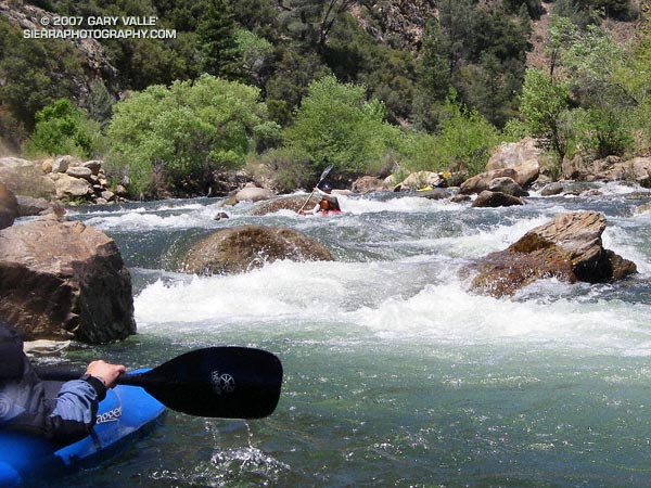 A kayaker waits in an eddy, while two other paddlers work their way through the last third of Limestone rapid, one of the classic class IV rapids on the upper Kern River.