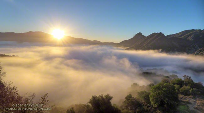 The sun rises over the shoulder of Saddle Peak illuminating a shallow layer of fog in Malibu Canyon.
