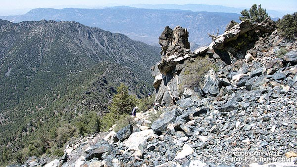 Three climbers pick their way through the rubble on the southwest ridge of Owens Peak.