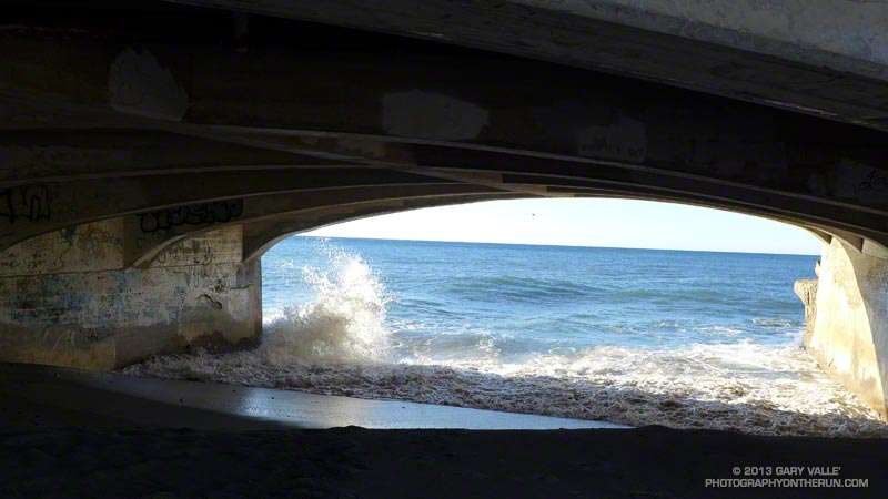 Riding the peak of a 6.5 foot high tide, a wave crashes into the bridge abutment on PCH at Sycamore Canyon.