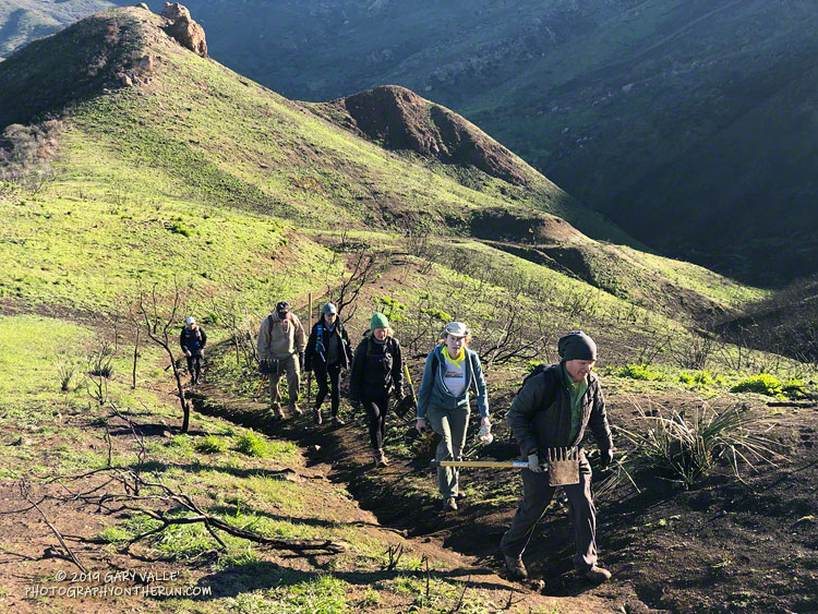 Members of the Santa Monica Mountains Trail Council (SMMTC) approaching the junction of the Old Boney and Chamberlain Trails. Trail runners assisted the SMMTC crew in repairing a part of the Chamberlain Trail damaged in the Woolsey Fire. February 23, 2019.
