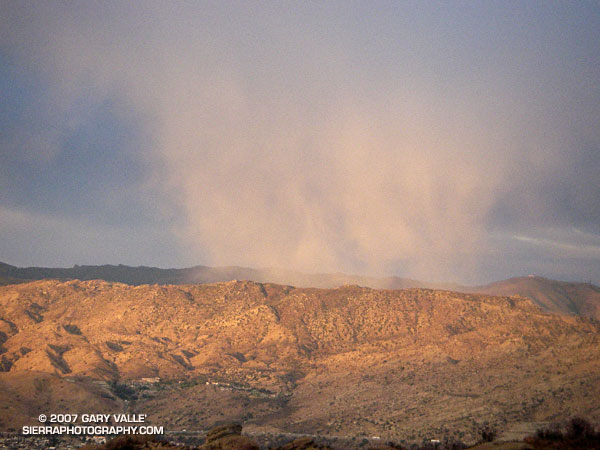 Low angle rays of the setting sun highlight a snow shower over the Rocky Peak