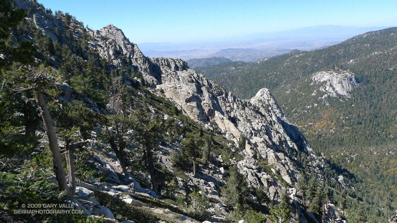 Tahquitz Rock (at the lower end of the rocky ridge), and Suicide Rock (across the valley) from the Pacific Crest Trail near Tahquitz Peak. Mt. Baldy area peaks can be seen in the distance.